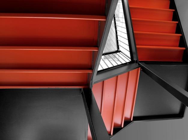 Escadas laranja de um prédio ao lado de um espelho