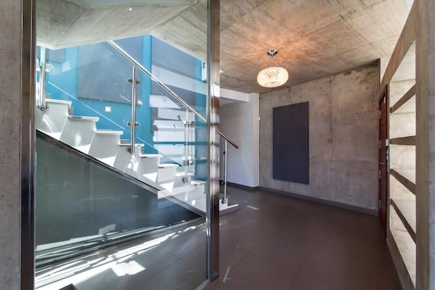 Escadas no interior da moderna casa de concreto, com parede azul e luminária.