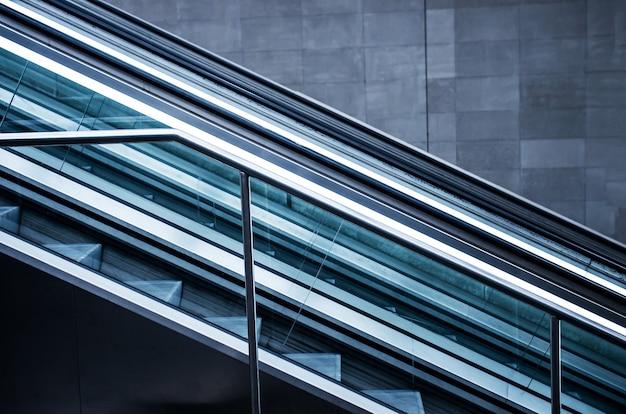 Escadas rolantes em um prédio com paredes cinza
