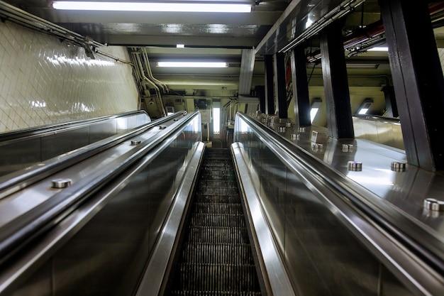 Escadas rolantes mecânicas para pessoas subindo e descendo no metrô