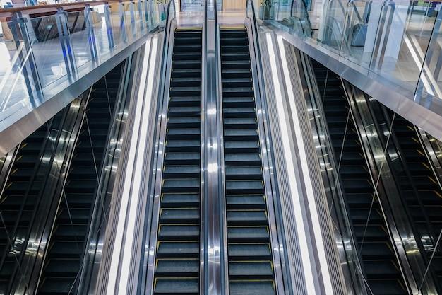 Escadas rolantes modernas de luxo com escada no aeroporto