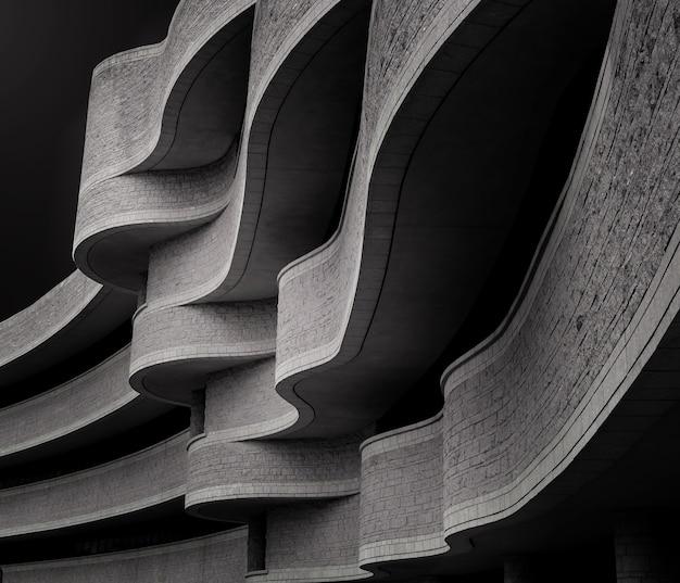 Escala de cinza de baixo ângulo de um edifício com arquitetura brutalista moderna sob a luz do sol