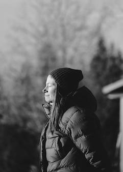 Escala de cinza do perfil lateral de uma garota com os olhos fechados sob a luz do sol em um fundo desfocado