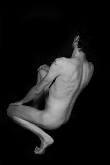 Escala de cinza vertical de um homem nu sentado no chão isolado no preto