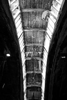 Escala de cinza vertical de um teto enferrujado de um edifício antigo durante o dia