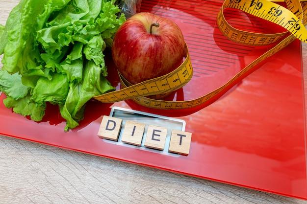 Escala eletrônica digital com fita métrica, alface, maçã, dieta de letras, conceito de emagrecimento.
