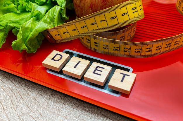 Escala eletrônica digital com fita métrica, alface, palavra dieta, conceito de emagrecimento.
