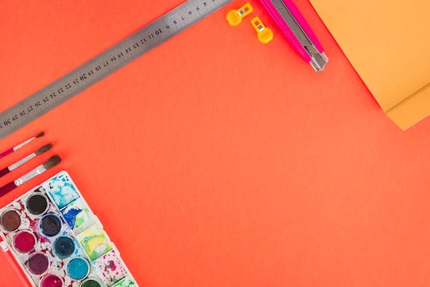 Escala; paleta de cores de água; escovas e cortador em pano de fundo laranja