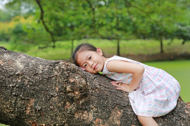 Escalada adorável da menina da criança pequena e descanso no tronco de árvore grande no jardim exterior.