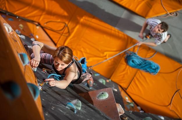 Escalada de mulher com carabinas e corda em uma parede de escalada indoor