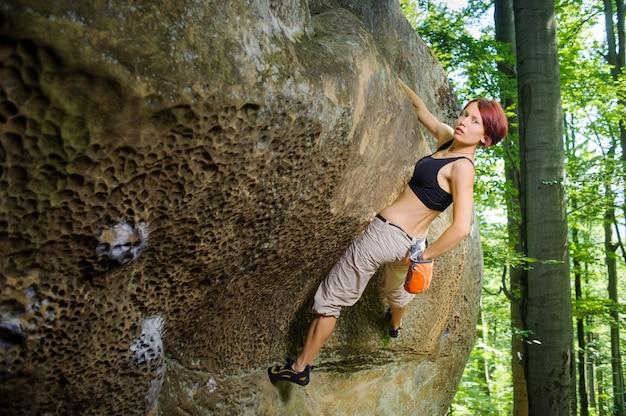 Escalador em grande rocha, pendurado por um lado