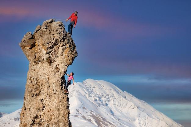 Escaladores masculinos e femininos com a guia que segura o parceiro