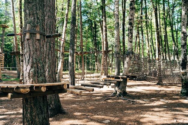 Escalando o parque no alto da pista de obstáculos das árvores no desafio de atividades esportivas ao ar livre do parque de diversões