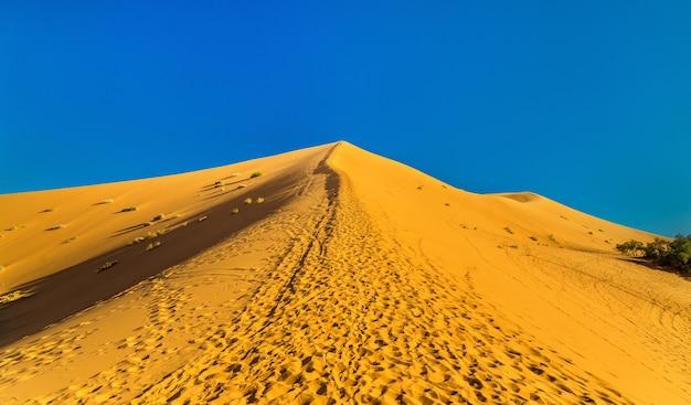 Escalando uma duna erg chebbi em merzouga, no marrocos