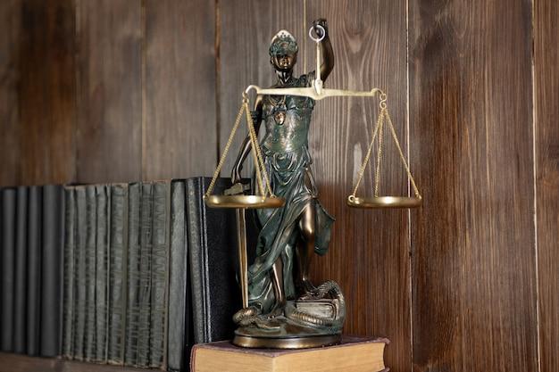 Escalas da justiça, senhora justiça, conceito de biblioteca jurídica, livros de direito em segundo plano.
