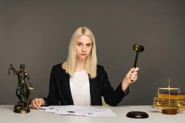 Escalas de justiça, martelo de justiça e documento de litígio, advogada trabalhando no escritório de advocacia.