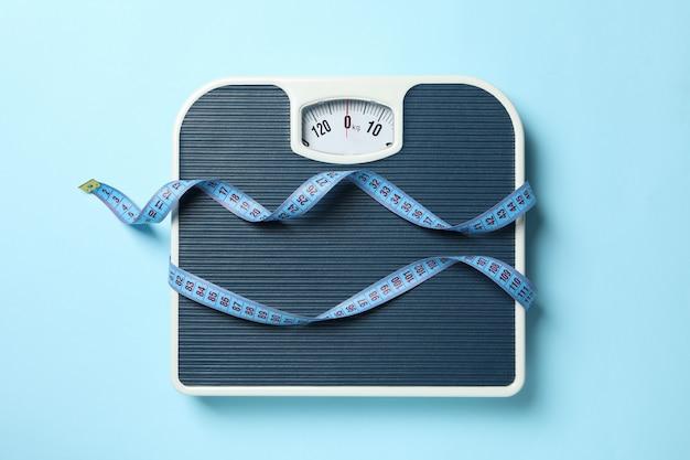 Escalas e fita métrica no chão azul. conceito de perda de peso