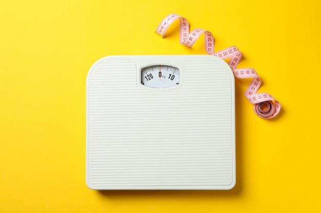 Escalas e fita métrica no piso amarelo. conceito de perda de peso