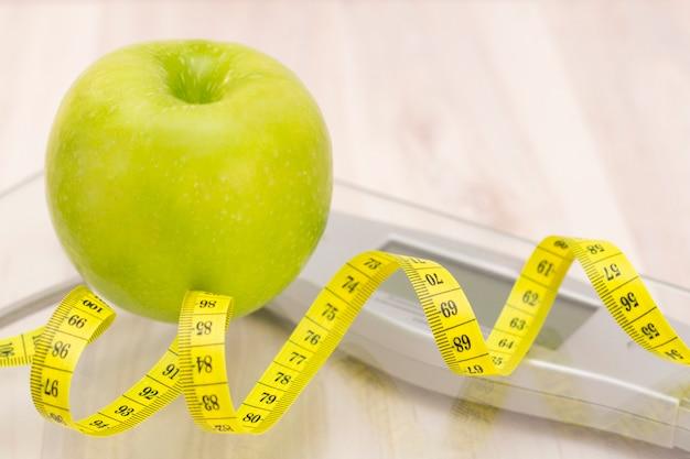 Escalas, maçã verde, fita métrica sobre uma superfície de madeira clara. preparação para a temporada de verão e praia, perda de peso e conceito esportivo