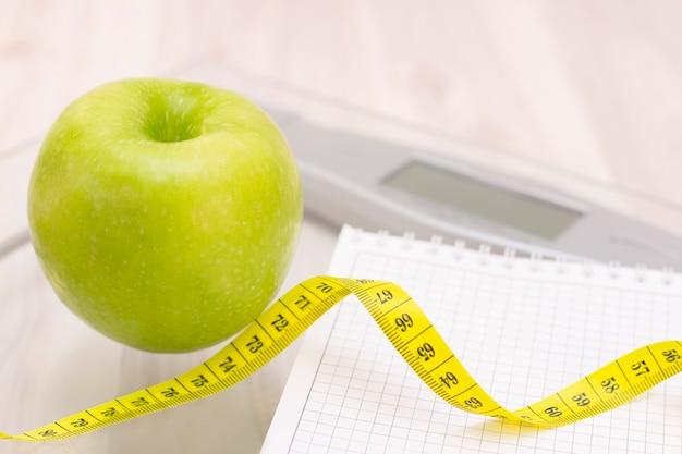 Escalas, uma maçã verde, uma fita métrica e um caderno para escrever sobre uma superfície de madeira clara. preparação para a temporada de verão e praia, perda de peso e conceito esportivo