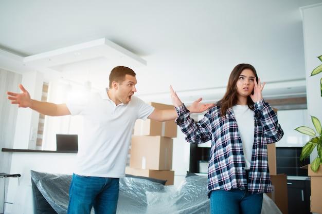 Escândalo durante a mudança para um novo lar. jovem casal brigando em um apartamento novo perto de caixas de papelão e.