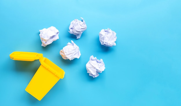 Escaninho amarelo com papel amassado branco sobre fundo azul.