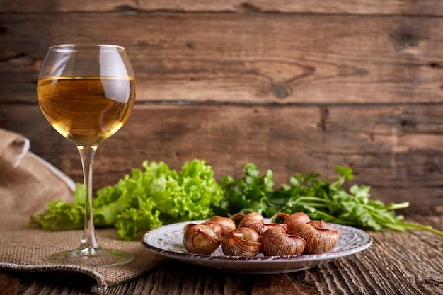 Escargots de bourgogne - caracóis com manteiga de ervas no fundo de madeira