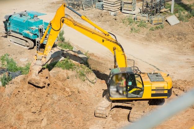 Escavadeira amarela cava solo em uma construção