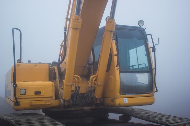 Escavadeira amarela e dia de nevoeiro.