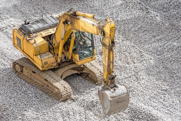 Escavadeira amarela em entulho trabalhando pedras de nivelamento no canteiro de obras.