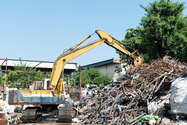 Escavadeira amarela em usina de reciclagem