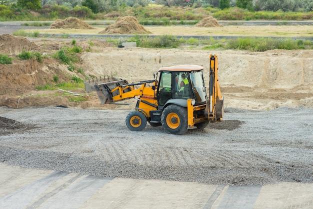 Escavadeira amarela nivelando cascalho em uma construção