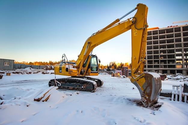 Escavadeira amarela no fundo de uma nova casa monolítica em construção no inverno