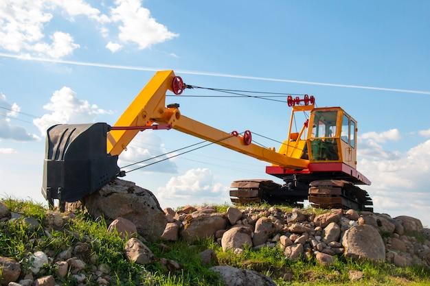 Escavadeira amarela no local de construção de pedra com balde preto em um dia ensolarado, conceito de construção
