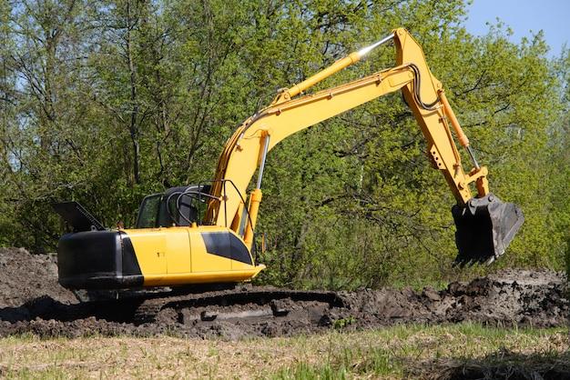 Escavadeira antes do dia útil de escavação contra floresta
