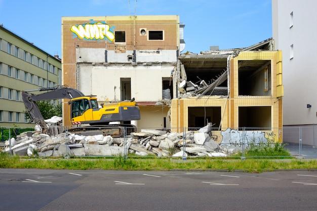 Escavadeira ao lado de prédio abandonado, pronto para demolição