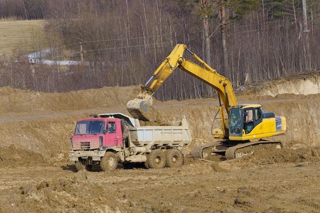 Escavadeira carregando caminhão basculante basculante em caixa de areia