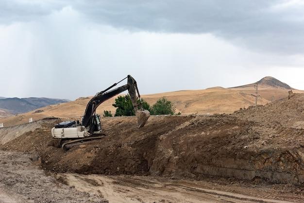 Escavadeira cava o solo em uma caixa de areia