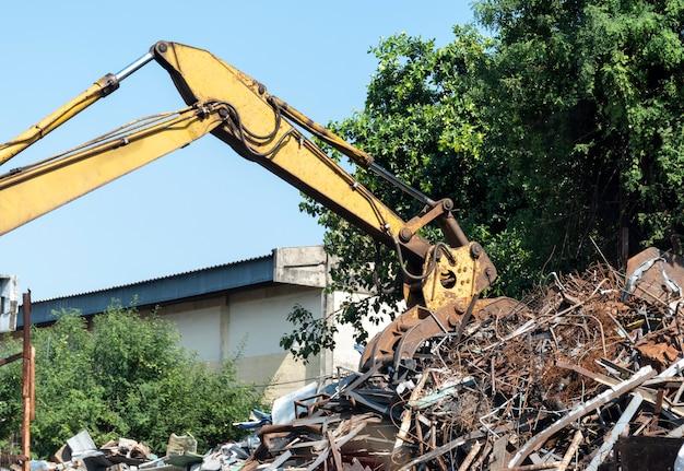 Escavadeira de cilindro de braço amarelo em usina de reciclagem