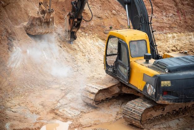 Escavadeira de perfuração no topo de rochas no local de construção de infra-estrutura de fundação