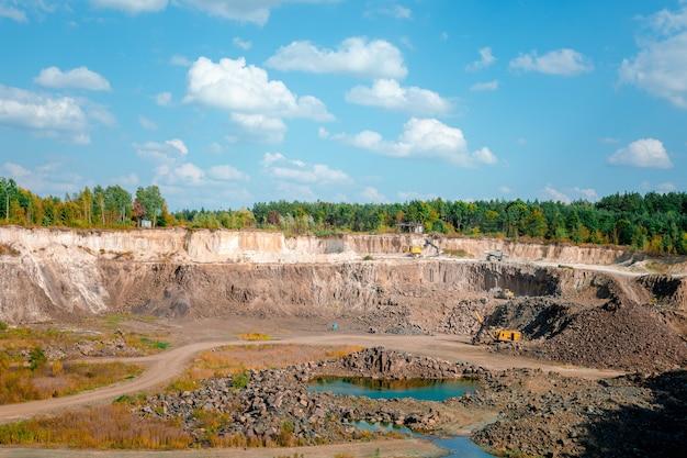 Escavadeira e caminhões pesados de mineração em uma pedreira de calcário