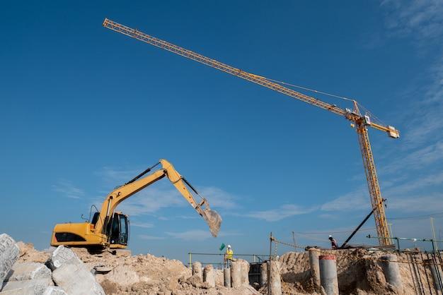 Escavadeira e guindaste de torre no canteiro de obras