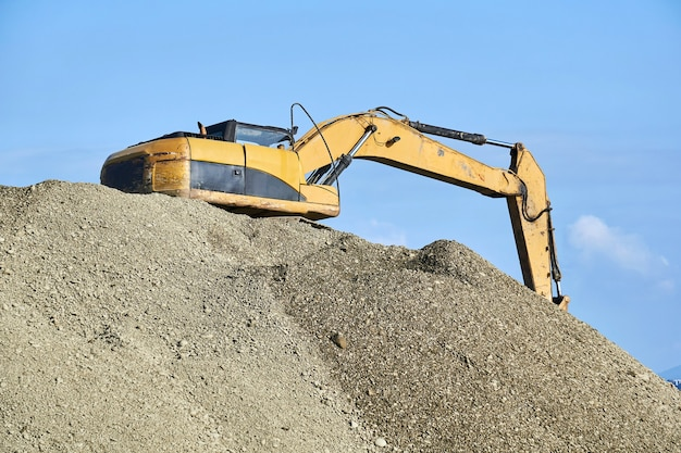 Escavadeira está em uma pilha de escombros contra o fundo do céu