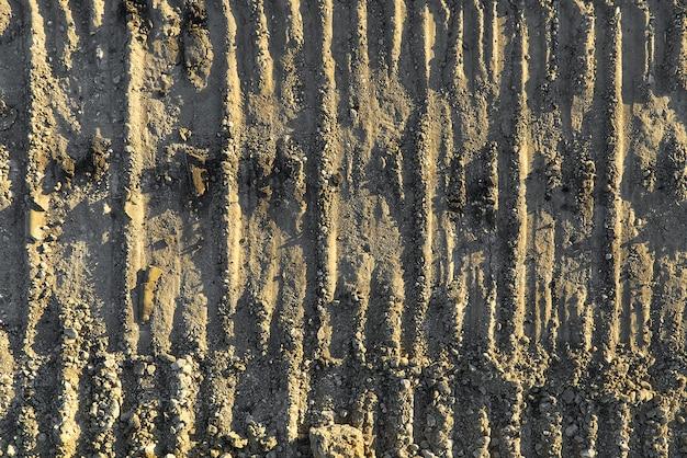 Escavadeira faixas sobre a textura do solo.