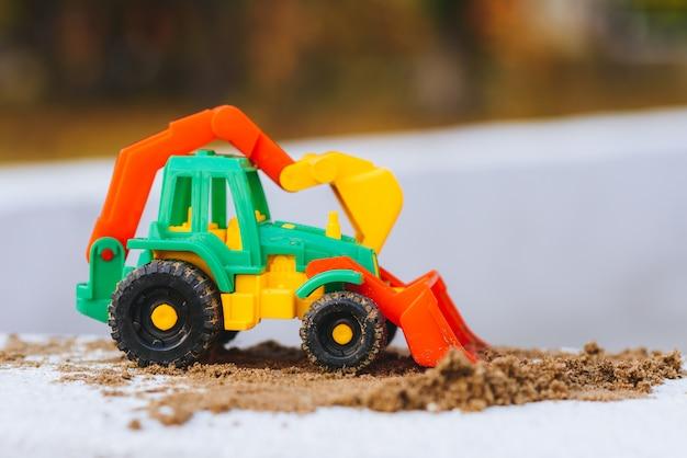 Escavadeira infantil em um close de caixa de areia