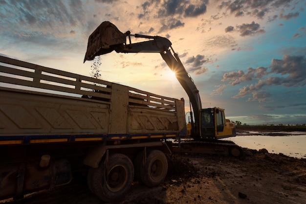 Escavadeira na caixa de areia durante obras de terraplenagem, preenchendo um caminhão basculante com rocha e solo para preenchimento em um novo projeto de construção de estradas de desenvolvimento comercial