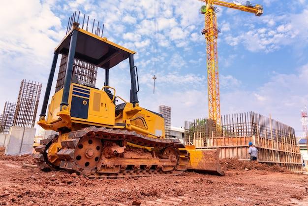 Escavadeira para trabalhar com terra e areia em caixa de areia na obra de fundação do edifício