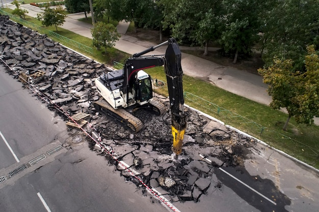 Escavadeira quebrando a superfície da estrada de concreto com broca hidro-martelada na reparação de estradas.