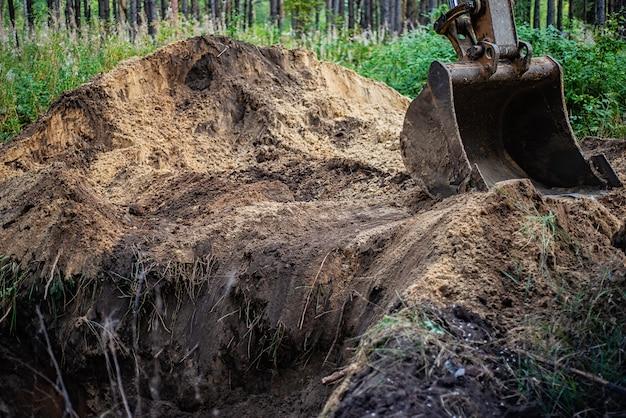 Escavadeira realiza trabalhos de escavação cavando o solo com um balde