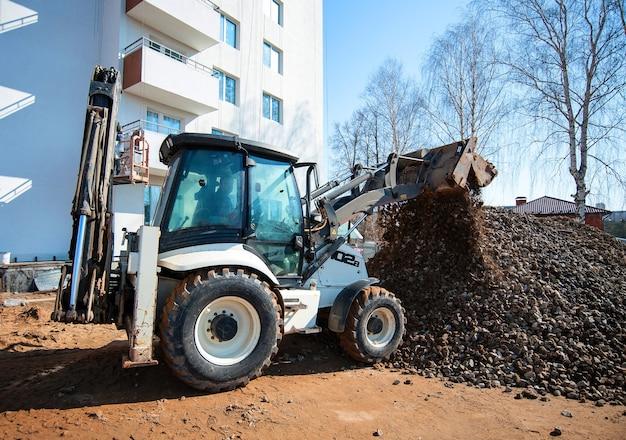 Escavadeira remove pedras no canteiro de obras de uma nova casa